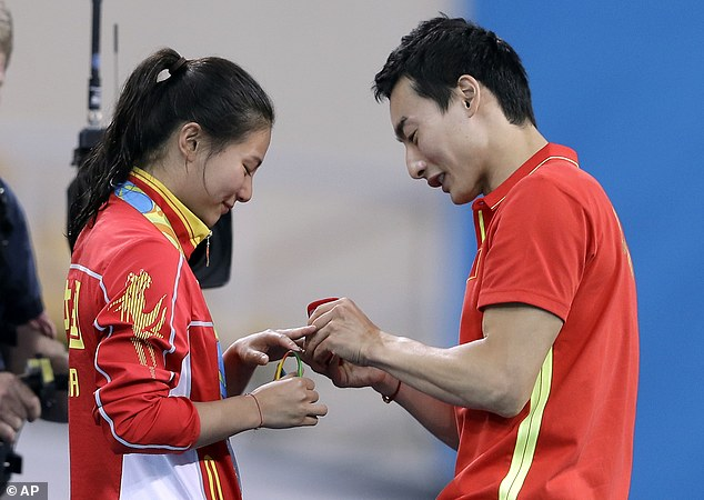 China's silver medalist He Zi, left, receivers a marriage proposal by China's diver Qin Ki, right, during the medal ceremony for the the women's 3-meter springboard diving final in the Maria Lenk Aquatic Center at the 2016 Summer Olympics in Rio de Janeiro, Brazil, Sunday, Aug. 14, 2016. (AP Photo/Michael Sohn)