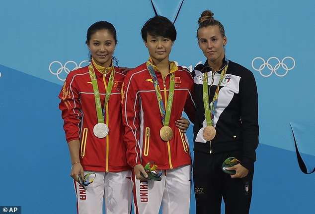 China's gold medalist Shi Tingmao, center, silver medalist He Zi of China, left and Italy's bronze medalist Tania Cagnotto, right, stand on the podium during the medals ceremony for the women's 3-meter springboard diving final in the Maria Lenk Aquatic Center at the 2016 Summer Olympics in Rio de Janeiro, Brazil, Sunday, Aug. 14, 2016. (AP Photo/Wong Maye-E)