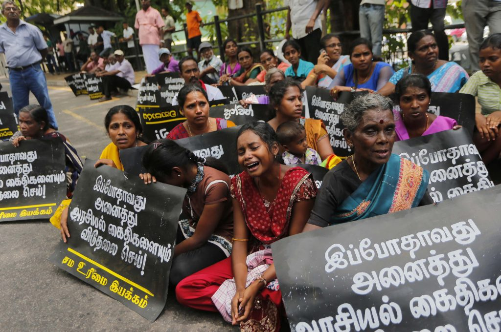 "FILE - In this Wednesday, Oct. 14, 2015 file photo, family members of ethnic Tamil detainees sit for a silent protest in Colombo, Sri Lanka. Sri Lanka's government has pledged to quickly process hundreds of ethnic Tamils who have been detained without charges for years on suspicion of links to former Tamil Tiger rebels. Placards read ""Release all political prisoners now."" (AP Photo/Eranga Jayawardena, File)"